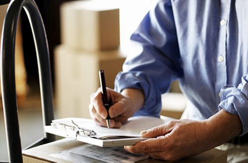 Shipping documents being reviewed and held by a businessman's hands.